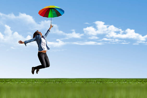Young woman is jumping with umbrella stock photo