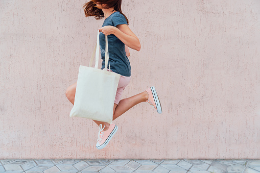 Young woman is jumping with white cotton bag in her hands. Mock up.