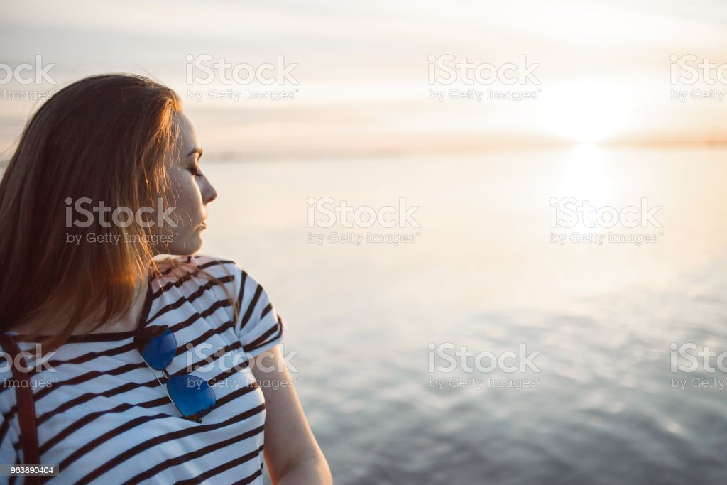 A young woman is looking at the sunset over a sea or river with beautiful soft sunny reflections in water - Royalty-free Adult Stock Photo