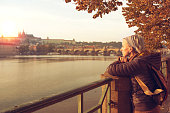 A young woman is looking at the sunset over a river Vltava in the city Prague. The old historical buildings are in the background.