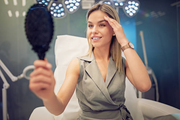 Young woman is looking her face in the mirror after beauty treatment procedure stock photo