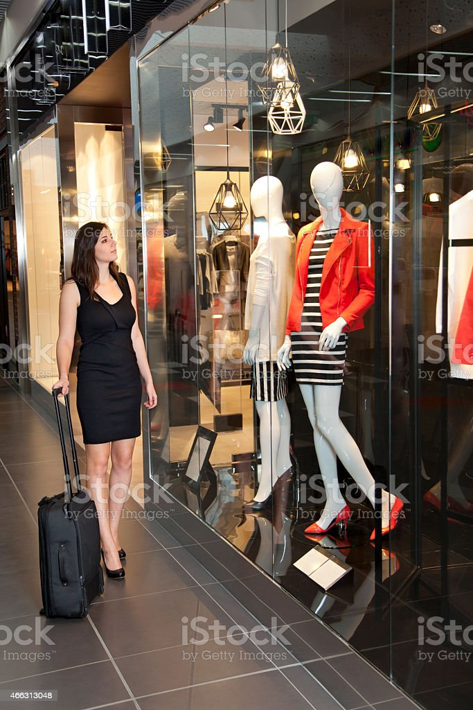 Young woman is looking into shop windows with fashion clothes stock photo