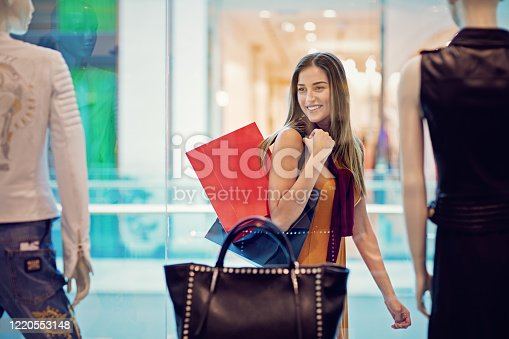 Young woman is looking store window in the Mall