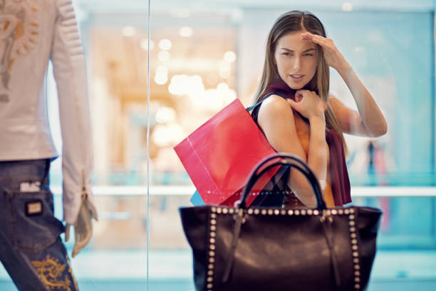 Young woman is looking store window in the Mall stock photo