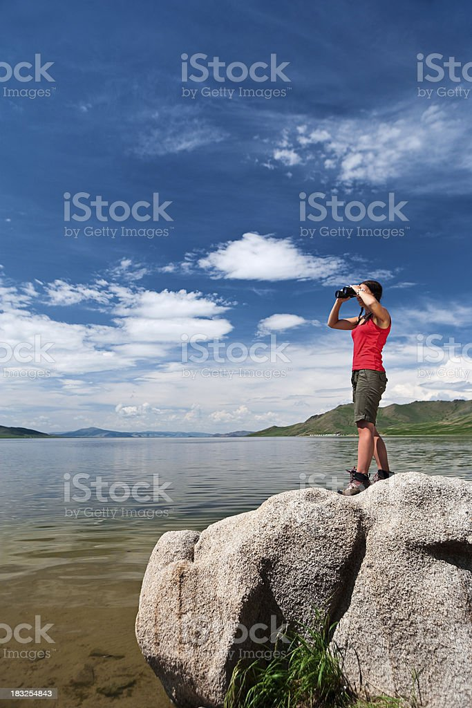 Young woman is looking through a binoculars stock photo
