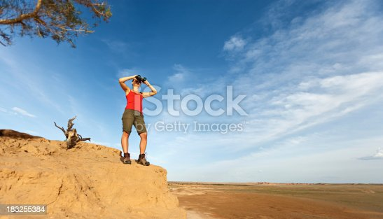 833314292istockphoto Young woman is looking through a binoculars 183255384