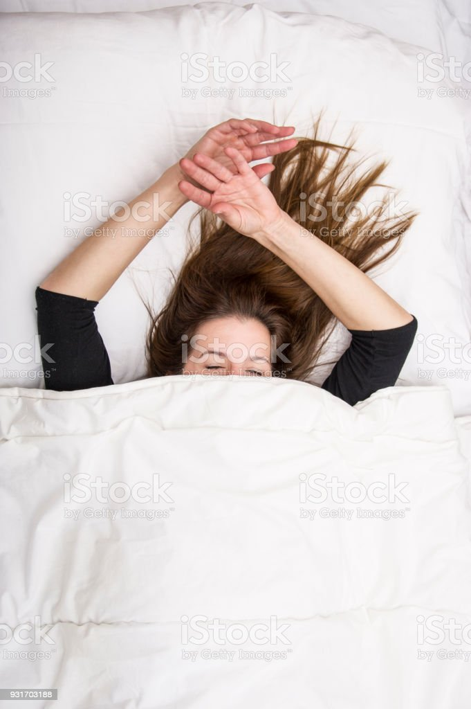Young woman is lying in her bed with closed eyes, smiling under her blanket after a restful sleep. stock photo