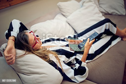 istock Young woman is lying on the sofa and watching TV 851305266