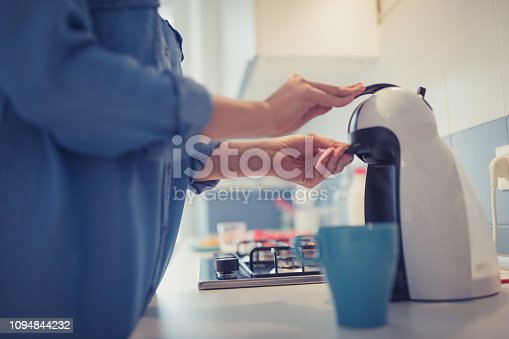 Young woman is making her morning coffee in her kitchen. She is wearing only a blue shirt. She is just waken