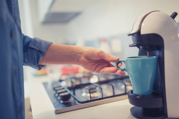 young woman is making morning coffee in her kitchen. - coffee maker stock pictures, royalty-free photos & images