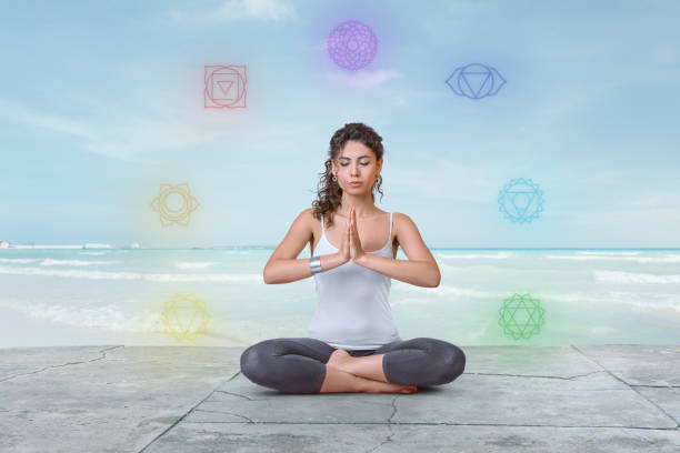 Young woman is meditating on the beach with chakras glowing around her