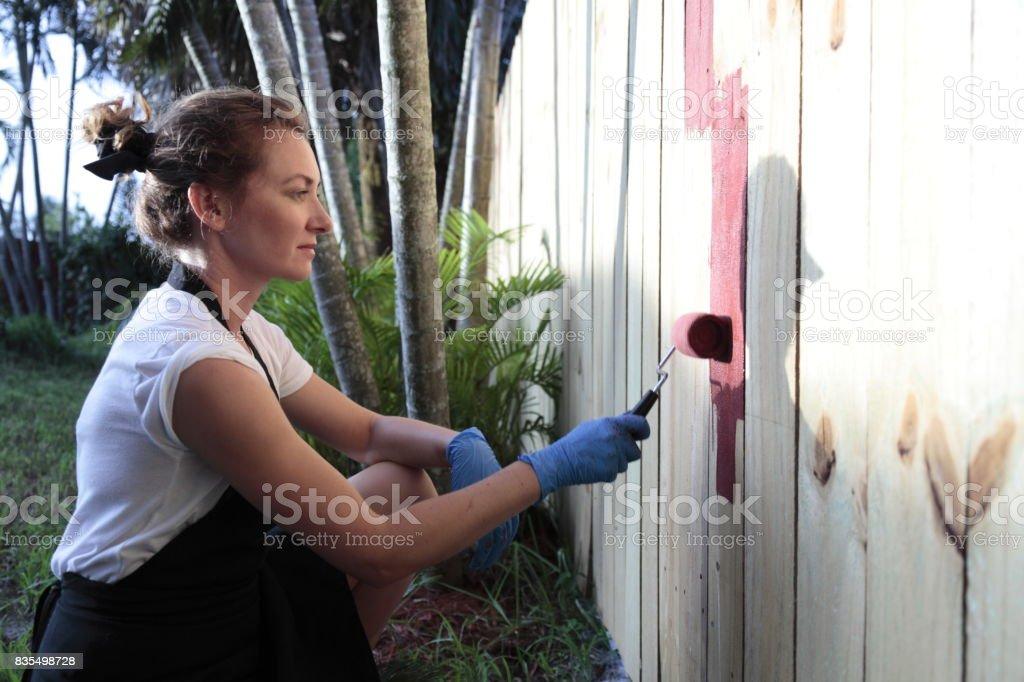 Jeune femme la peinture est-elle une clôture. - Photo