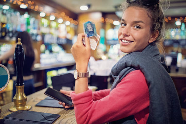 Young woman is paying her bill in a bar stock photo