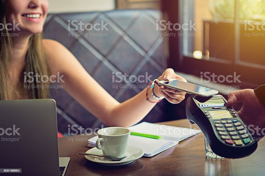 Young woman is paying in the cafe stock photo
