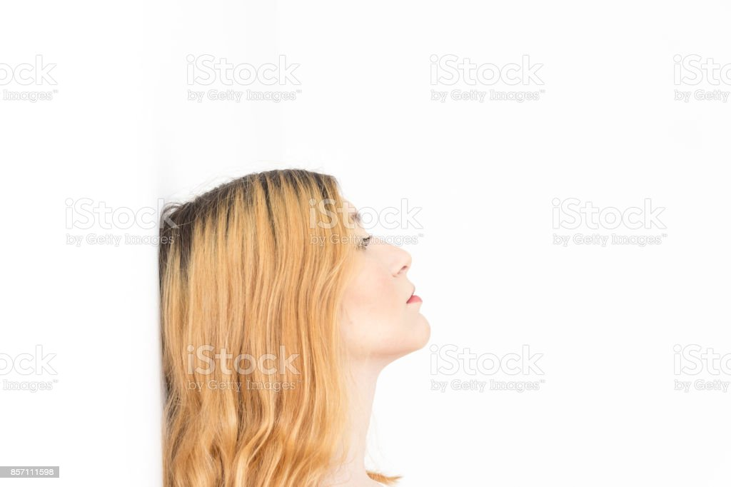Young woman is pensive. She is blonde with her head propped against the wall and looks at infinity. White background and well lit stock photo