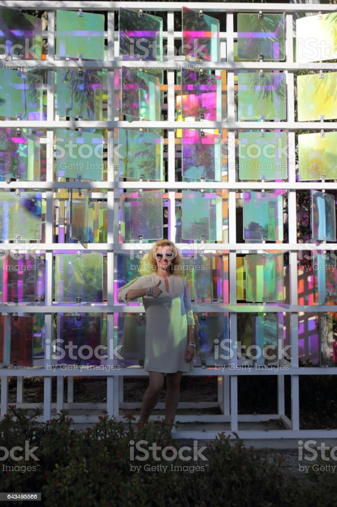 Young woman is playing with color kaleidoscope hotspots. stock photo