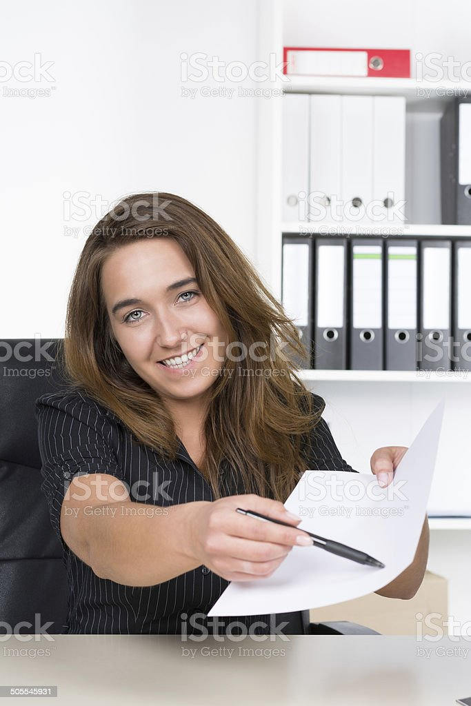 Young woman is pointing at a document with a pen stock photo