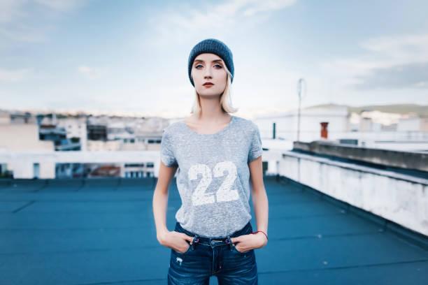mujer joven está posando en una azotea con traje de calle de estilo urbano - moda playera fotografías e imágenes de stock