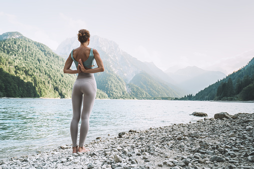 Young woman is practicing yoga at mountain lake. Girl doing yoga on nature. Healthy lifestyles.
