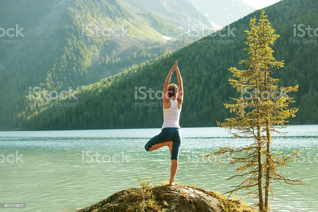 Young woman is practicing yoga at mountain lake stock photo