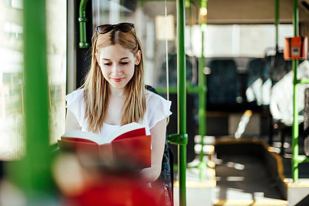 junge frau liest ein buch während der fahrt - bahn bus stock-fotos und bilder