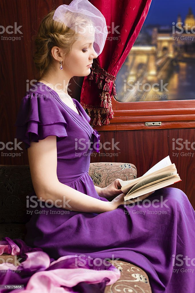 Young woman is reading the book in train royalty-free stock photo