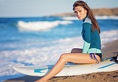 Young woman is resting and enjoying the ocean after windsurfing