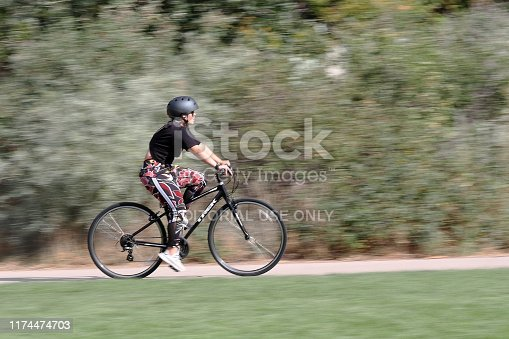 Denver, Colorado - September 7, 2019: A young woman is riding a bicycle path. Motion blur background