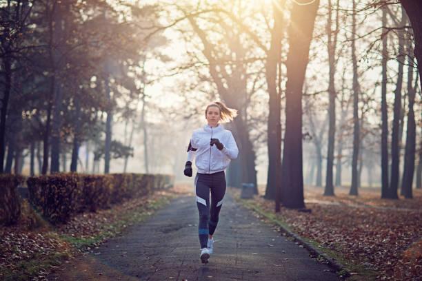 junge frau läuft in den kalten, nebligen morgen - joggerin stock-fotos und bilder