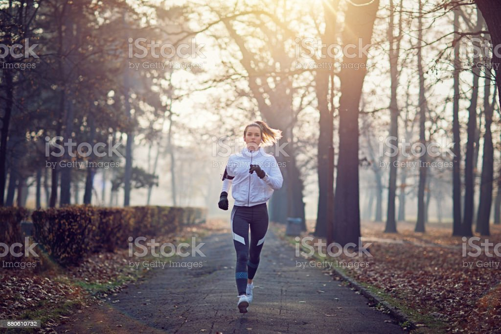Young woman is running in the cold foggy morning stock photo