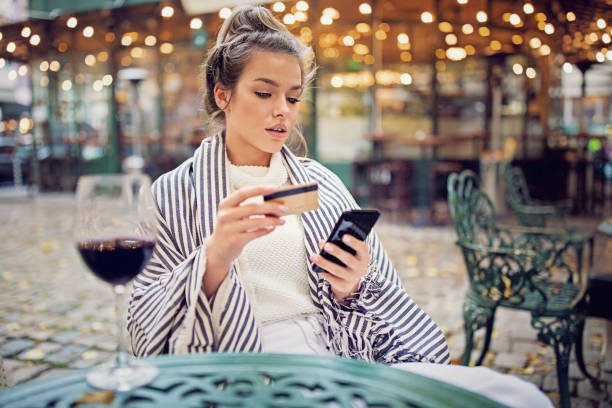 Young woman is shopping online using her credit card and mobile phone stock photo