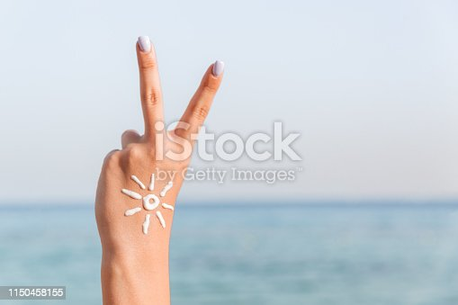 Young woman is showing peace gesture and has sun shape on her hand at the beach.