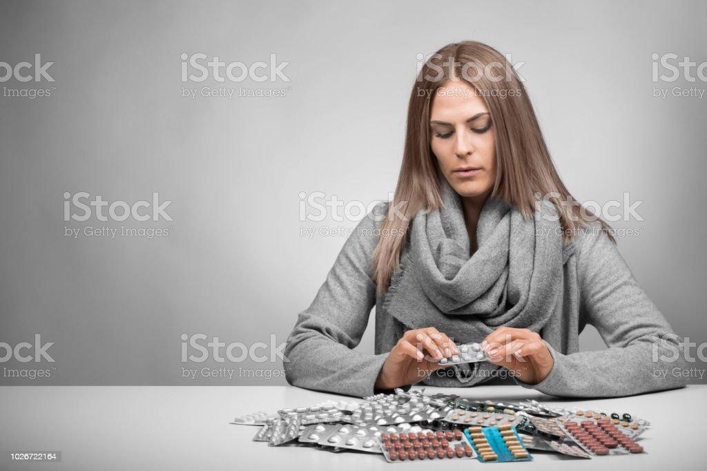 Junge Frau sitzt vor viele Pillen – Foto