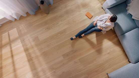 Young Woman is Sitting on a Floor and Looking out of the Window after Reading a Book. Cozy Living Room with Modern Interior, Grey Sofa and Wooden Flooring. Top View Camera Shot.