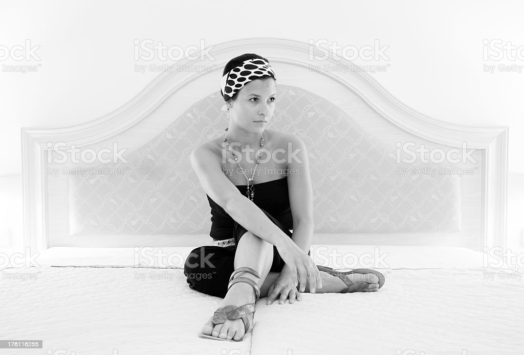 Young woman is sitting on bed stock photo