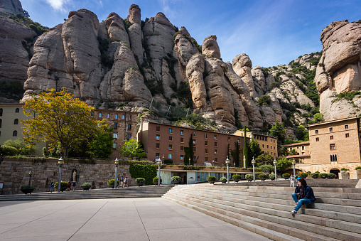 Young woman is sitting on steps among buildings of Montserrat monastery located between huge rocks in Catalonia, Spain