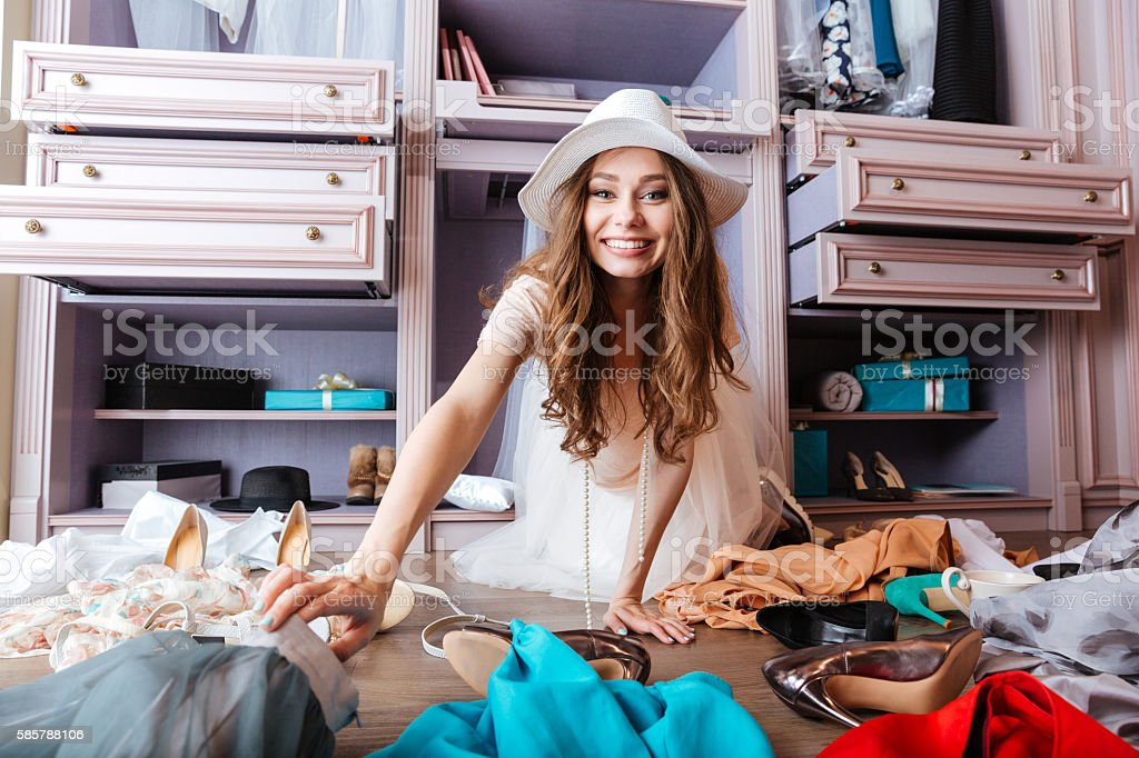 Young woman is sitting on the floor with clothes stock photo