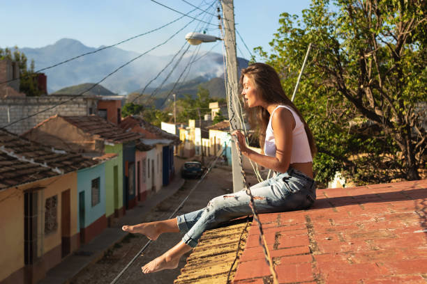 Young woman is sitting on the roof of old house stock photo