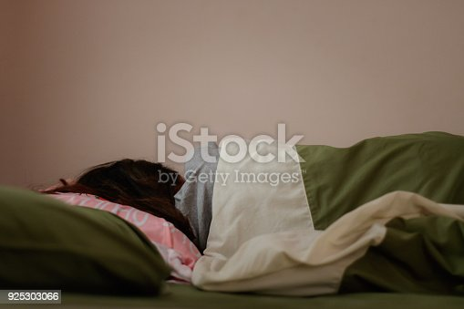 istock Young woman is sleeping from the back in bed 925303066