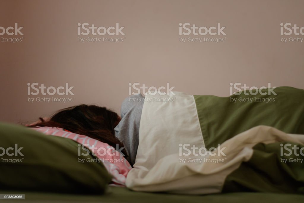 Young woman is sleeping from the back in bed stock photo