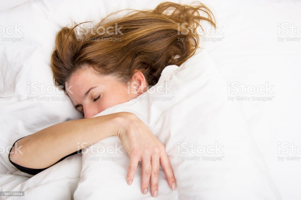 Young woman is sleeping in her bed. stock photo
