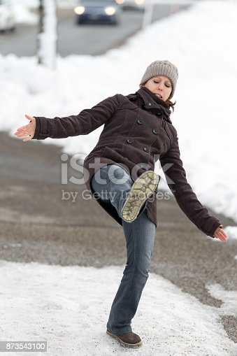 istock young woman is slipping and falling on street 873543100