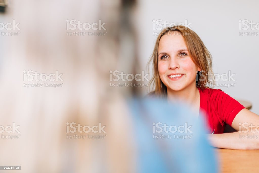 A young woman is smiling and listening at a social worker