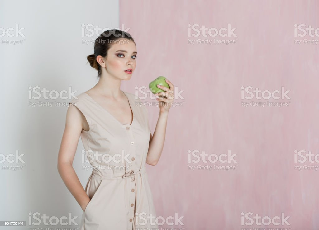 A young woman is standing and holding a big green apple in her hand royalty-free stock photo