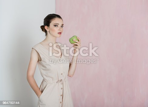 A Young Woman Is Standing And Holding A Big Green Apple In Her Hand Stock Photo & More Pictures of Adult