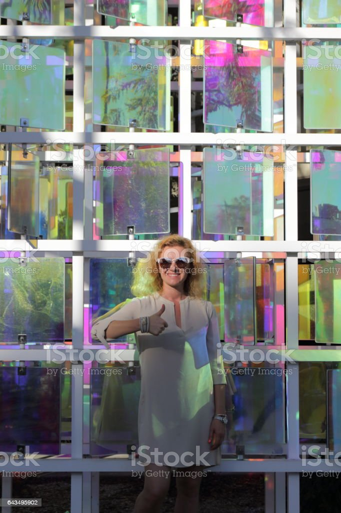 Young woman is standing near the color kaleidoscope. stock photo
