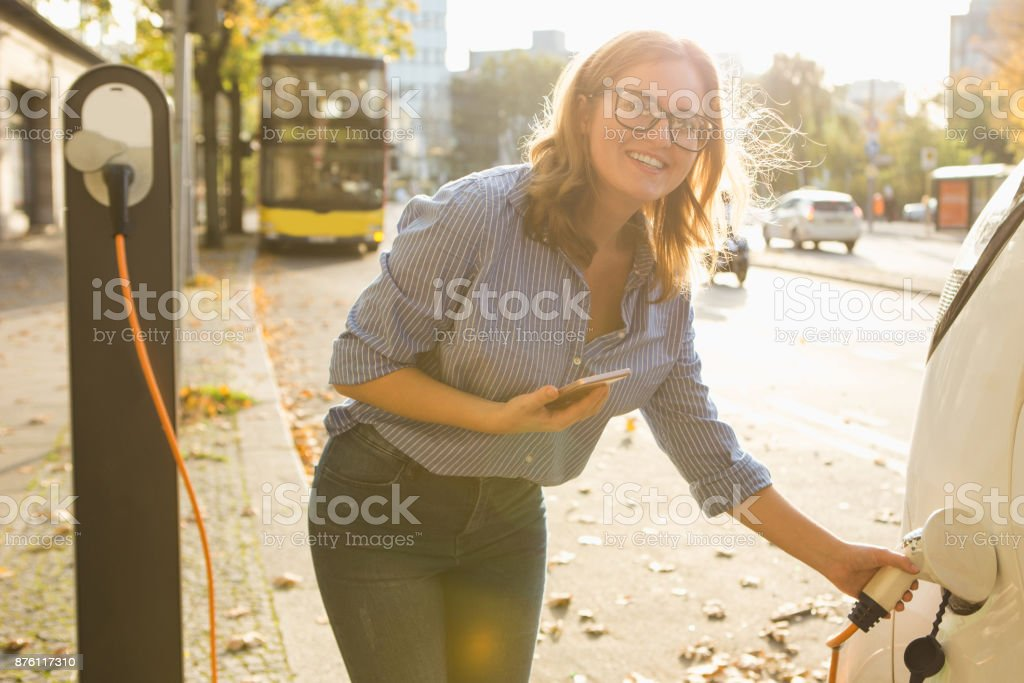 Young woman is standing near the electric car and holding smartphone - foto stock