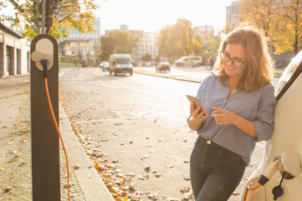 young woman is standing near the electric car and holding smartphone - automobile con biodiesel foto e immagini stock