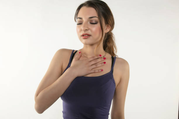 a young woman is struggling with pain, isolated on background - esophagus stock photos and pictures