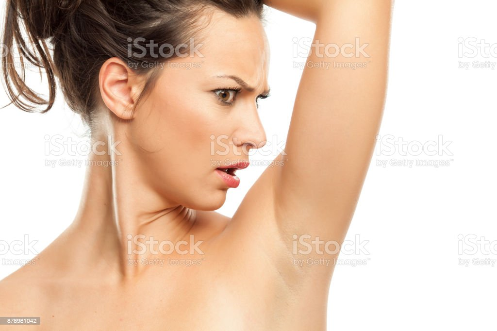 A young woman is surprised by the scents of her armpits stock photo